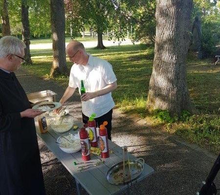 P. Cosmas mit Sauerländer Getränk bereitet die Speisen
